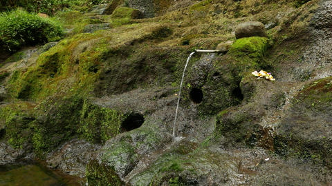 Water trickle from rill hold in steel pipe, against moss-covered rocks Footage