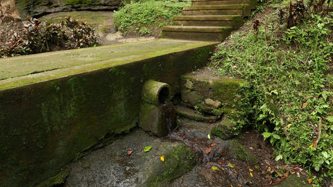 Small water outlet and tiny stream trickle through, mossy concrete way Footage