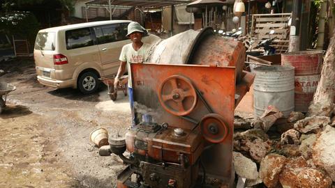 Poor man put cement into concrete mixer, loudly construction machinerymachine Footage