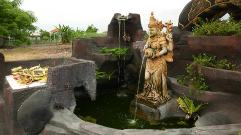 Tiny waterfall pond, Balinese Temple, Hindu sculpture with water stream from jug Footage