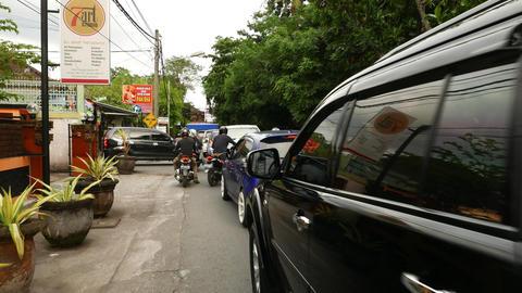 Traffic jam on balinese street, walk through sideway, car stand in line Footage