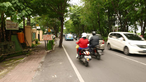 Busy rural road surrounded by tree foliage, rural Balinese street, moving camera Footage