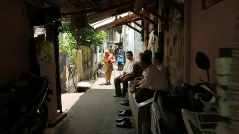 Woman come through narrow alley, man group sit looking aside Footage