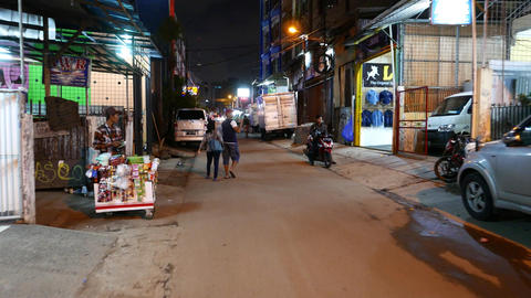 Couple walks on night alley, bright shops, modest means district Footage