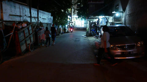 Woman throw out trash to container, night street, parallax shot Footage