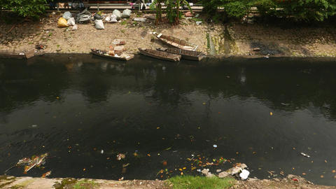 Black water polluted by fuel oil, trash float, small boats Live Action