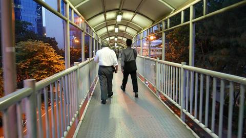 Younger man walks faster and outrun senior, pedestrian passage, follow camera Footage