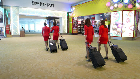 Air hostess in red suits run through duty free zone, hurry to flight boarding Footage