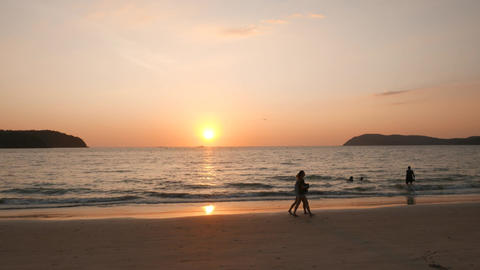 Tropical island beach sunset, people silhouettes, tracking shot Footage