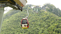 Cable cars hang move between stations, rainforest mountains, Langkawi Live Action