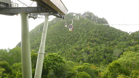 Cable car gondola departs from middle station, rainforest mountains Live Action
