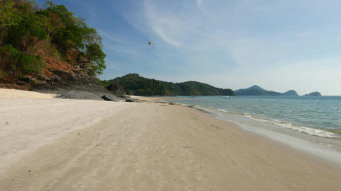 Pan view fine island beach, green trees, clear sand and calm water Live Action
