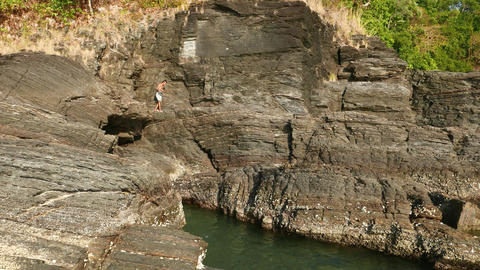 Young fisherman in slippers climb black basalt rocky shore, tropical island Footage