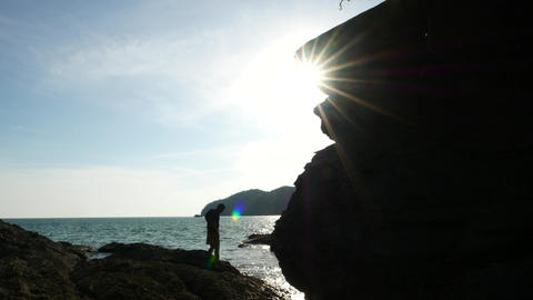 Man jump from rock to rock, high contrast stony cliff, back sun light Footage
