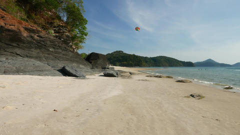 Move forward along beautiful beach, to rocky area and trees Footage