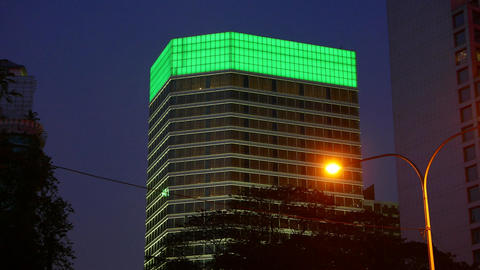 Illuminated billboard at skyscraper top, at dark sky. Color changes to green Footage