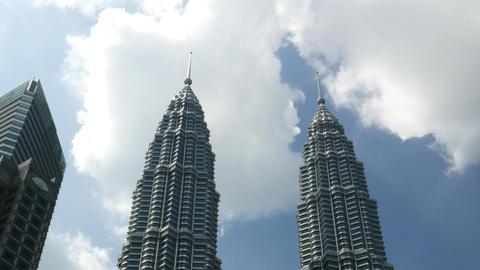 Tops of Petronas Twin Towers, panning shot, dark tree crowns Footage