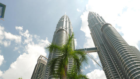Amazing Petronas Skyscrapers through palm trees, dolly shot Footage