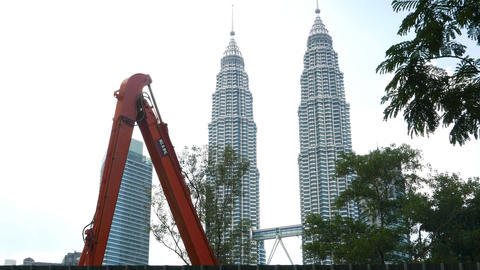 Excavator arm against Petronas Twin towers, construction digging Footage