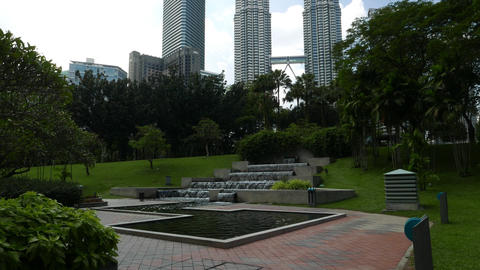KLCC Park waterfall, greenery and Petronas Twin Towers on the background Footage