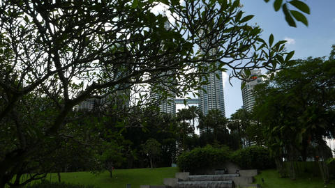 Petronas Twin Towers skyline through trees, long panning shot Footage