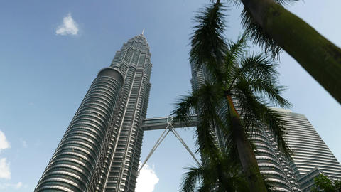 Looking up to Menara Petronas, right tower closed by palm trees, dolly shot Footage