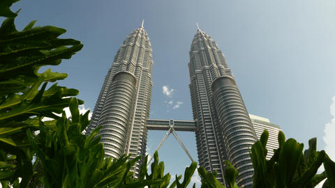 Tropical bush leaves on foreground, Petronas Twin Towers on background Footage