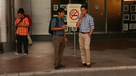 Two Men Smoking Against Prohibition Sign, No Smoke Area, Public Place stock footage