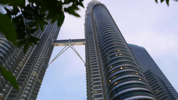 Bottom view Petronas Twin Towers in dusk, high angle, moving from trees Footage
