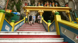 Climb up steps, passing Hindu arch at Batu Caves entrance, tourists on the way Footage