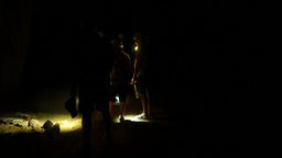People walking in dark cave flashlight spot on the floor and wall Footage