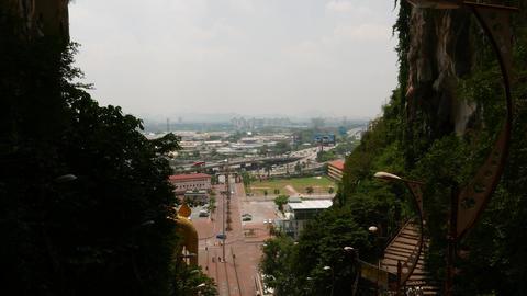 Kuala Lumpur cityscape skyline from Batu Caves entrance, panning up Footage