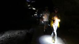 Group of cavers passing by on narrow path inside dark cave, flashlights Footage