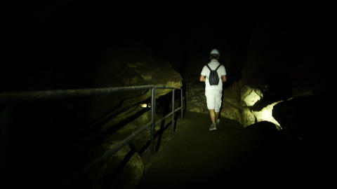 Cavers group walking through dark cave track, following behind Footage