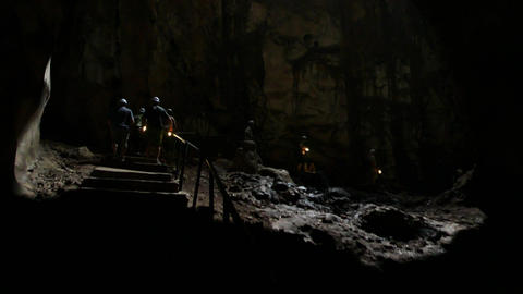 Cavers group walking in dim light under mystical cave vaults, dark cave Footage