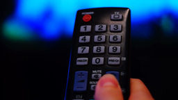 Remote control. Thumb touching the channel button on a remote Footage