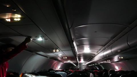 Landed aircraft cabin, dim light, little girl tune up air ventilation Live Action