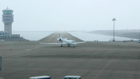 Business jet taxiing out from runway, aside the control tower Footage