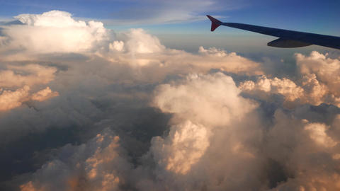 Clouds formations in sunset light, top view from aircraft window Live Action