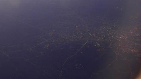 Night city lights aerial from aircraft window, glowing lines and roads Footage