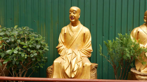Happy and irony faces of golden Buddha statues in row of many sculptures Footage