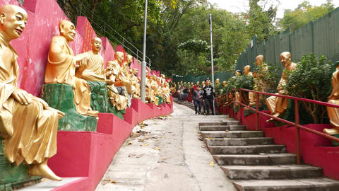 Climb up way to monastery, many gold Buddha statues on the way Live Action