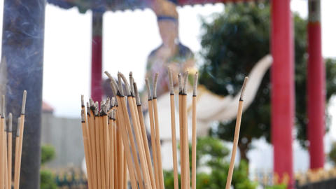 Smouldering incense sticks close up, against blurred Buddha statue Footage