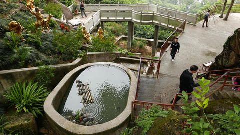 Little pond on hillside, tourists, belvedere walkway, monastery garden Footage