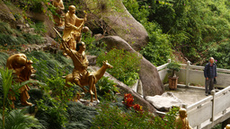Golden Buddha statues on grassy hillside. mirador and lonely tourist Footage