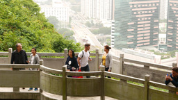 Mirador on mountain side, people watching up, against cityscape Footage
