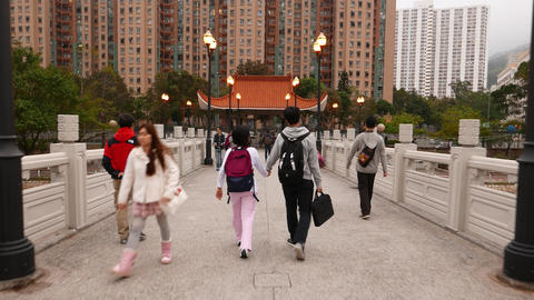 Young Chinese couple walking on the bridge, following camera Footage