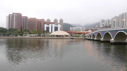 Park on opposite river side, buildings far away. Panning right to arched bridge Footage