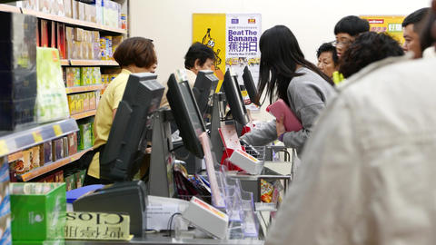 Woman working at cashier desk in department store, POV from queue Footage