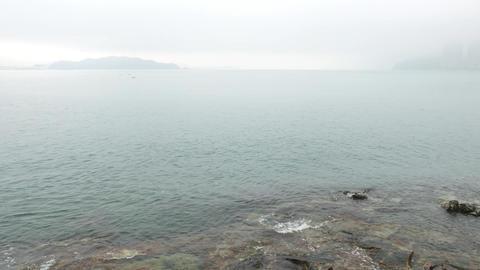 Rocky cliff at Yue Mun Point, haze horizon, fishermans on rocks Footage